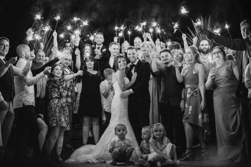 Forest Pines Hotel wedding photography. Guests surround bride and groom with sparklers lit.