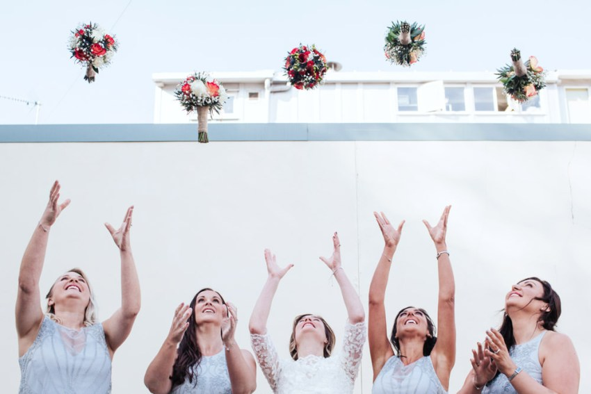 Biscuit Factory wedding photography, Newcastle. Bride and bridesmaids toss bouquets in air.