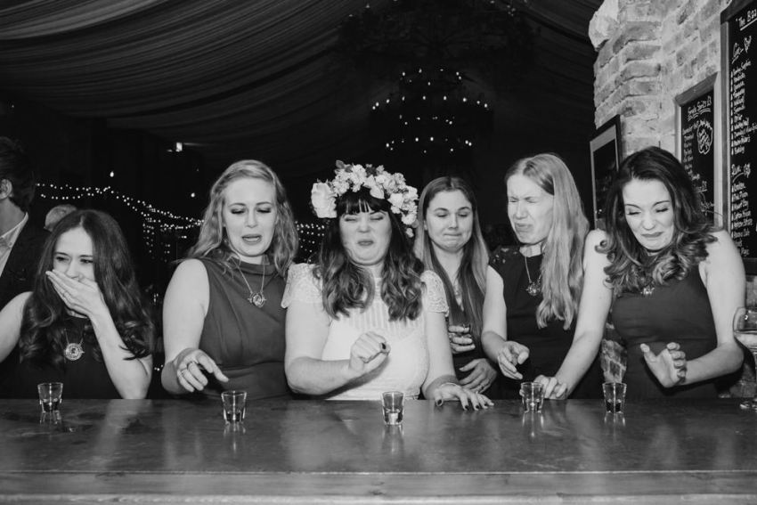 Bride and bridesmaids pull faces after drinking shots.
