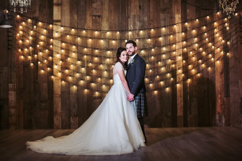 Wharfedale Grange wedding photography. Bride and groom portrait in front of strings of festoon lights.
