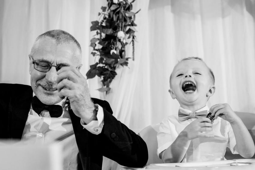 Granddad and grandson laughing during speeches.