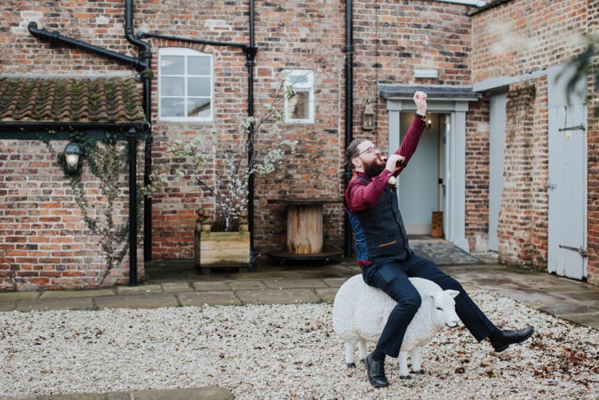 Groomsman rides plastic sheep while drinking beer at Hornington Manor.
