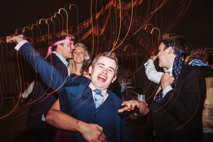 Wedding guests on dance floor with ties around their heads and swirling lights.