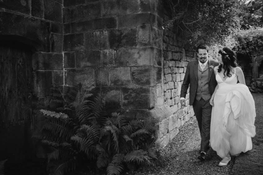 Bride and groom walk through the gardens at ERH.