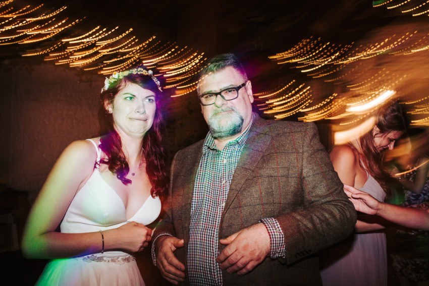 Bride pulls face while stood with her dad. Lights swirl in backdrop.