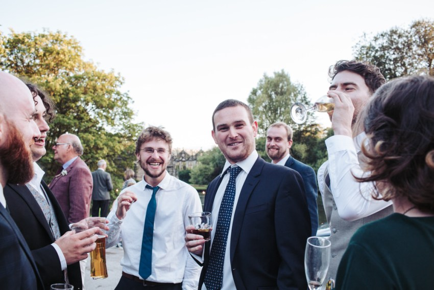 Wedding guests drinking outdoors at East Riddlesden Hall.
