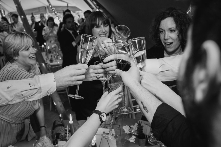 Guests clink champaign glasses at the end of the wedding speeches.