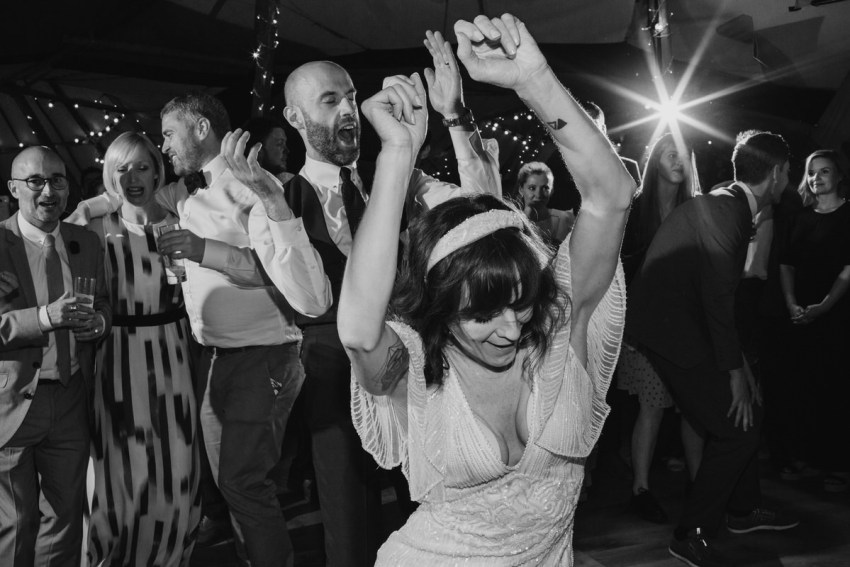Bride and groom dancing together, clapping and throwing arms in the air.
