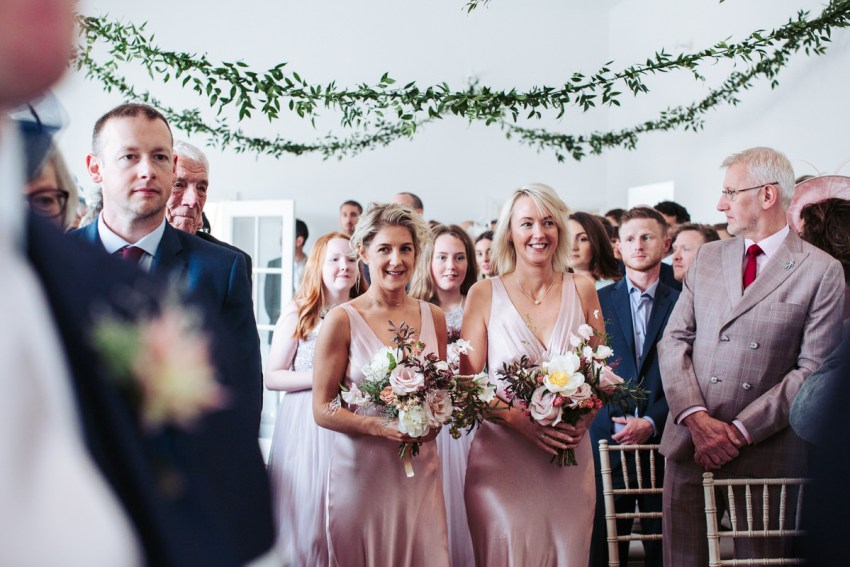 The bridesmaids walk down the aisle wearing pale pink silk dresses.