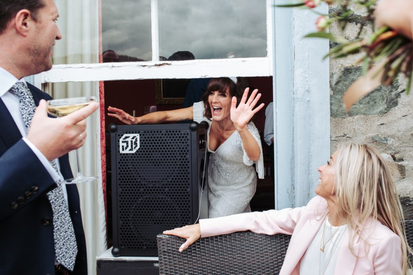 Bride waves while setting up a large speaker in the window at Silverholme Manor wedding.
