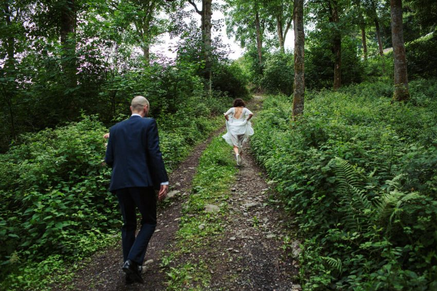 Bride picks up her dress and runs ahead up the woodland track.