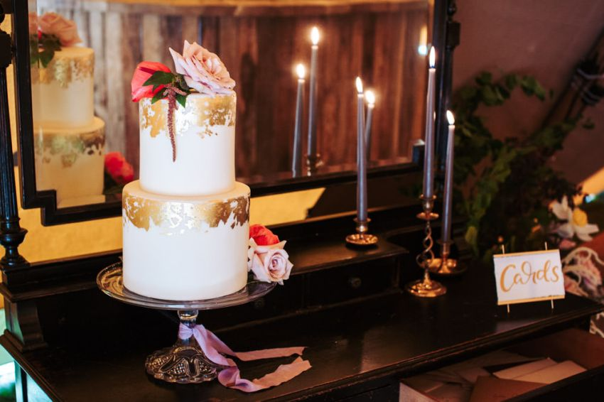 A two tier wedding cake in plain white with decorative gold leaf trimming.