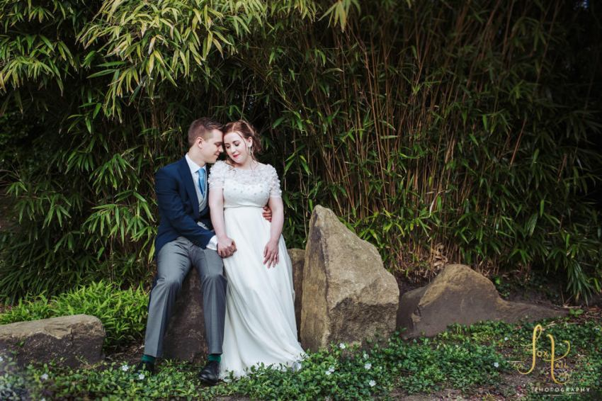 Sun Pavilion wedding photography in Yorkshire, UK. Bride and groom sit on rock in front of bamboo in Valley gardens.