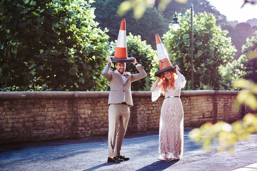 Arches wedding photography. Fun photo of bride and groom holding traffic cones on their heads.