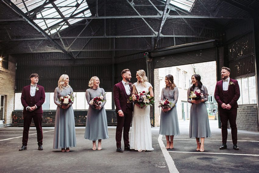 Arches industrial venue wedding photography, Leeds, Yorkshire. Bridesmaids wear grey dresses, groomsmen wear burgundy suits  in an industrial carpark.