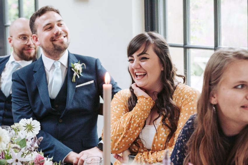 Guests laugh during the wedding speeches.