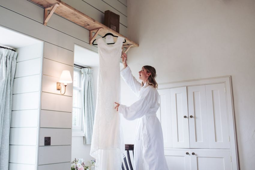 Bride reaches up to take down her hanging wedding dress.