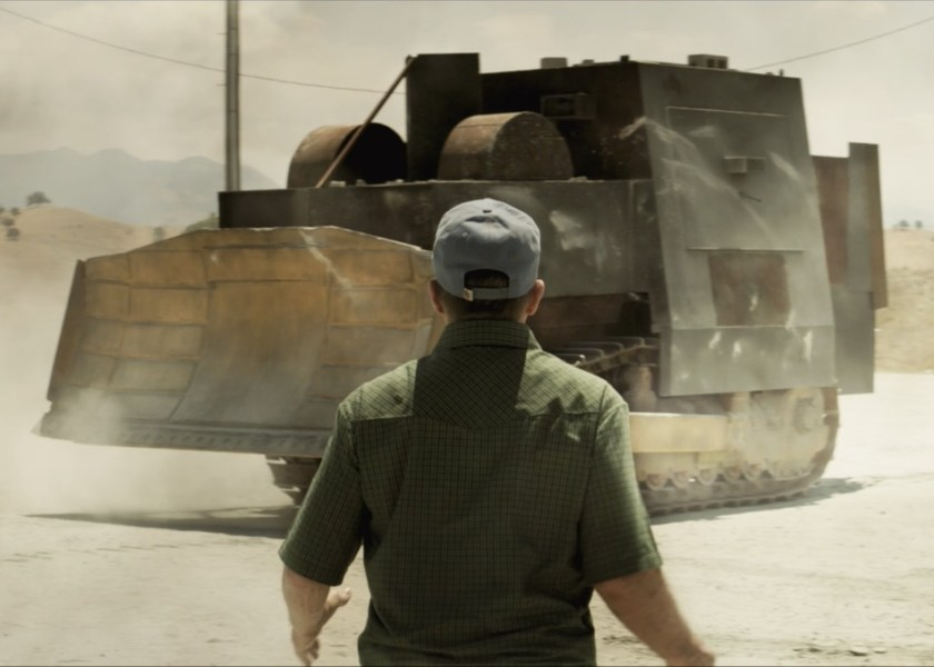 Man stands in awe of a fortified bulldozer.