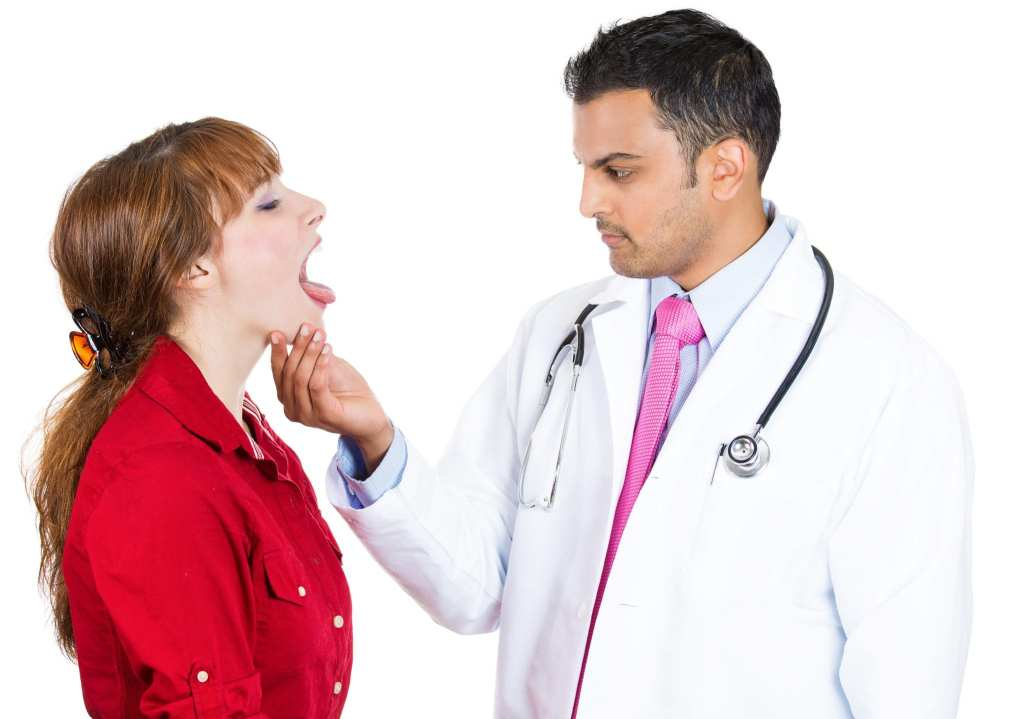 Doctor palpating under the jaw and looking in patient's mouth
