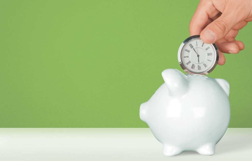 A small clock being placed in a white piggy bank on a green background