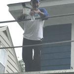 member helping paint habitat house