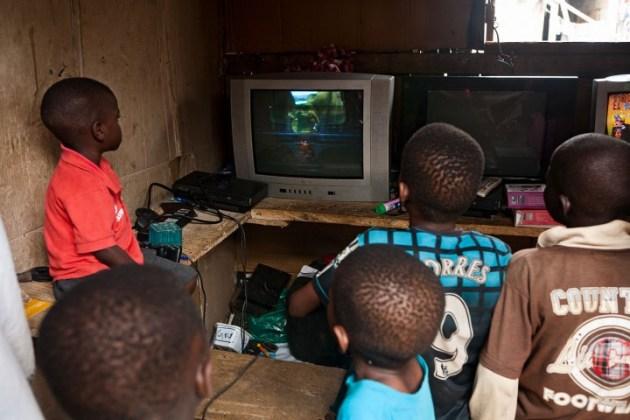 スラム街にある小さなゲームセンターで、PS2のゲーム『God of War』をプレイする子供たち。