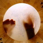 looking up through the skin o drum to see drummer playing percussion
