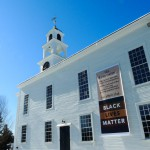 Black Lives Banner on the meeting house with snow and deep blue sky.