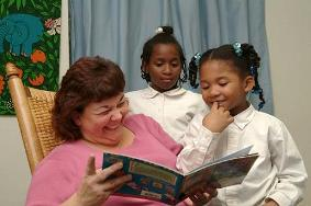 An IHN volunteer reads to guest children.