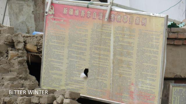 Les vestiges des murs présentent encore un tableau d'affichage sur lequel on peut lire « Règlementation sur les affaires religieuses de la région autonome ouïghoure du Xinjiang »