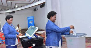 A woman testing machine a voter in DRC.
