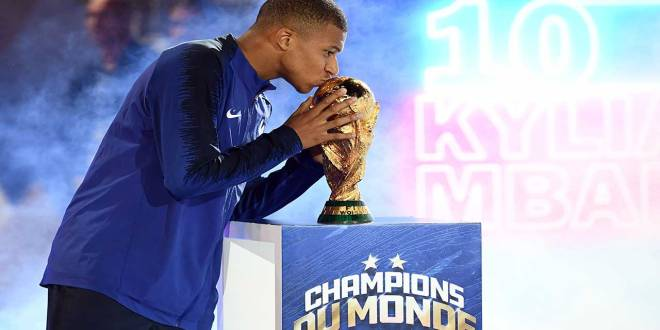 Kylian Mbappe kisses the 2018 World Cup trophy