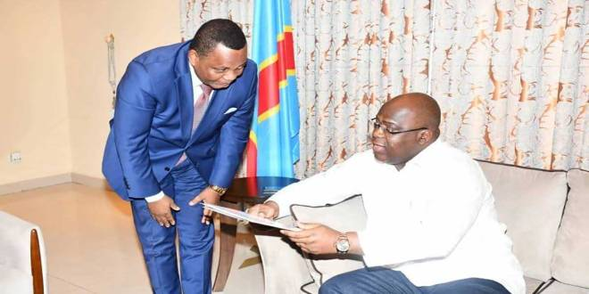 Fatshi, President de la RDC, assis en train de lire un document.