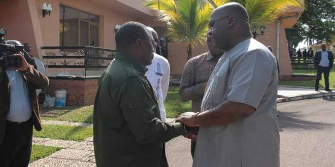 Joseph Kabila et Fatshi discutent, les mains croisées les unes sur les autres.