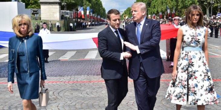 French President Macron shakes hands with US President Trump next to Macron's wife Brigitte Macron and US First Lady Melania Trump during the traditional Bastille Day military parade in Paris