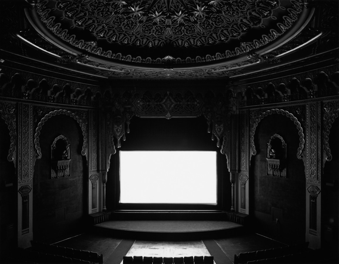 Black and white photograph of an empty theater with ornate detailing displaying a glowing white screen