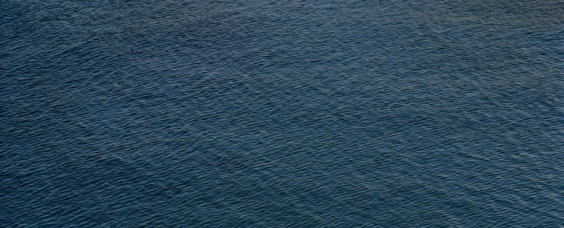 Color photograph of the rippled surface of a dark blue sea