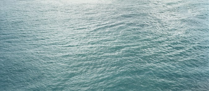 Color photograph of the surface of a calm blue ocean