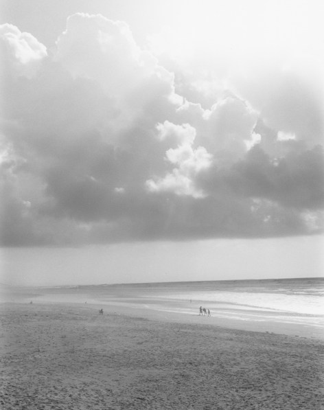 black-and-white vertical photo of brightly lit clouds over a beach
