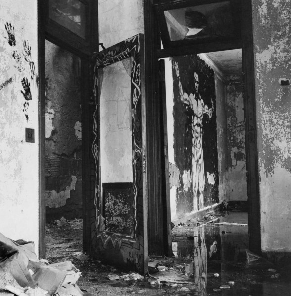 Black-and-white photograph of a derelict interior with a muscular man painted on a wall beyond a doorway