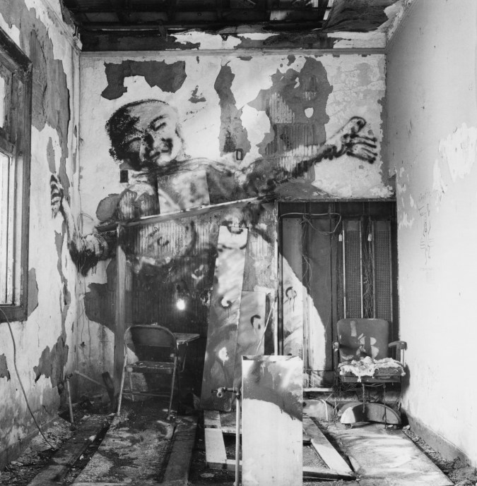 Black-and-white photograph of a derelict interior with a man painted on the wall