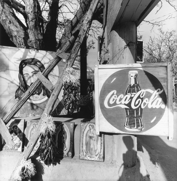 Black-and-white photograph of a Coca Cola sign and paintings of Jesus