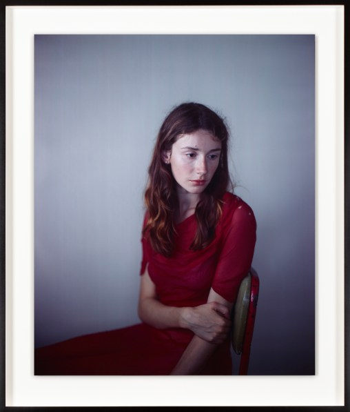 Color photographic portrait of a seated young woman with shoulder-length hair and a downcast gaze