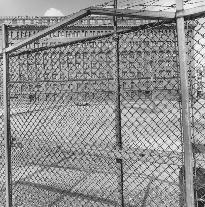 A black and white photograph of a chain link fence with a large structure in the background