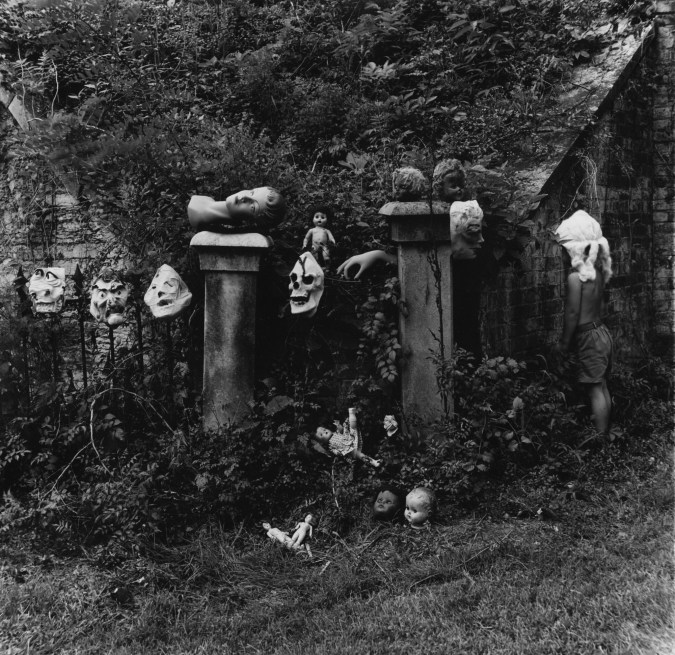 Black-and-white photograph of an assortment of rubber masks and doll heads positioned on two pedestals in an overgrown garden