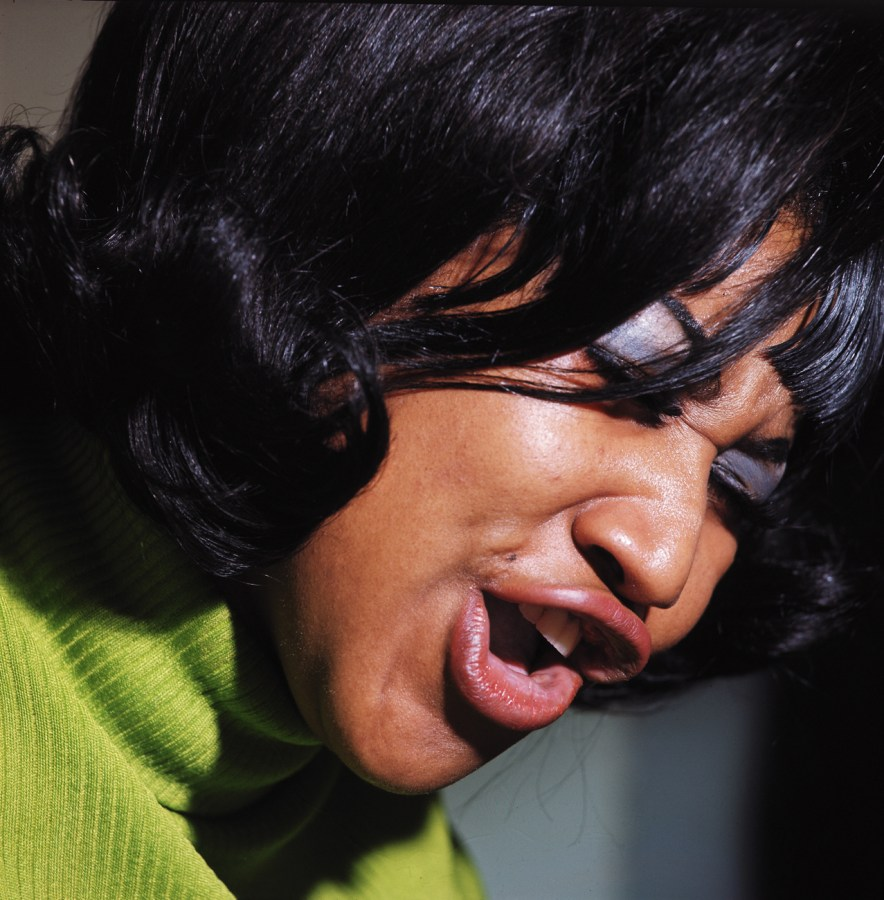 Up close color photograph of Aretha Franklin singing wearing a bright green sweater