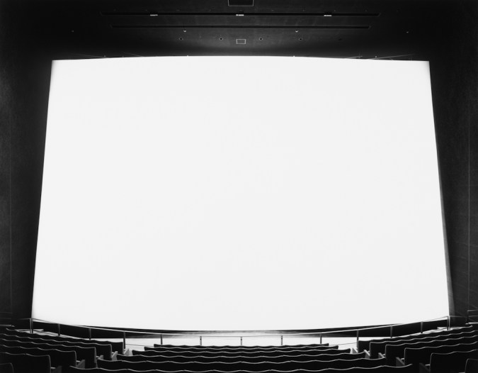 Black-and-white photograph of an empty movie theater with an extra large glowing white screen
