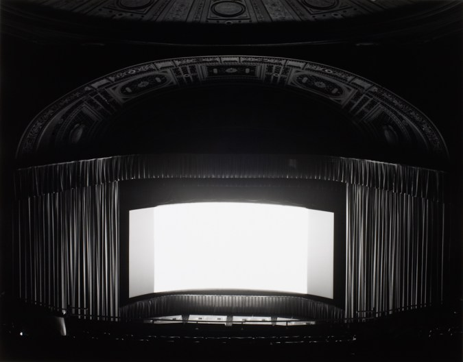 Black-and-white photograph of an empty theater with a glowing white screen onstage between parted curtains