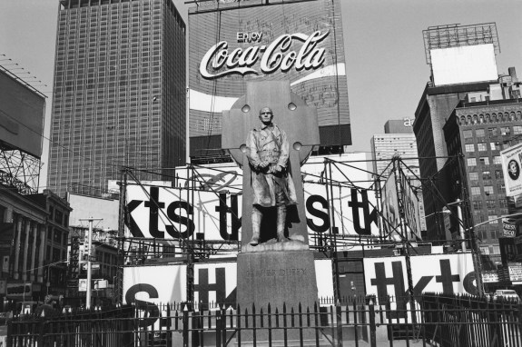 Black-and-white photograph of a statue with a Coca-Cola sign, billboards, and skyscrapers in the background