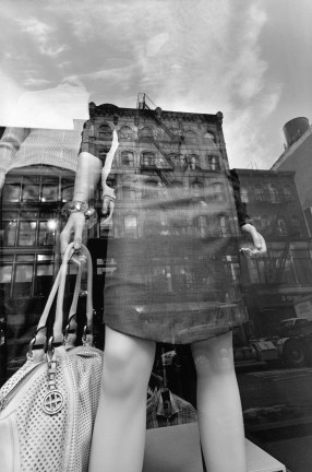Black-and-white photograph of the torso of a mannequin in a store front with buildings reflected in the glass